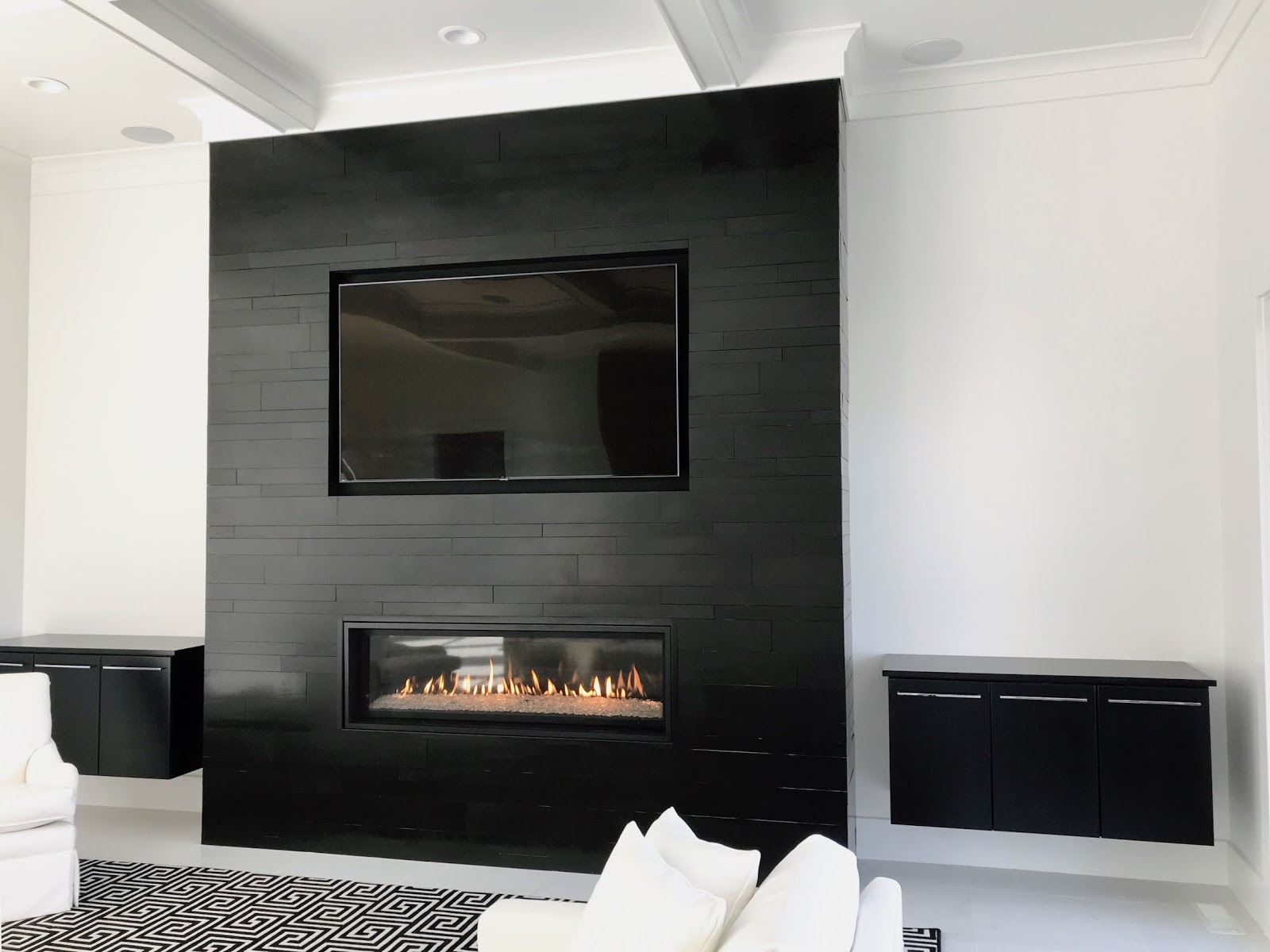 A modern fireplace remodel with granite tile, and a low-rise, electric fireplace