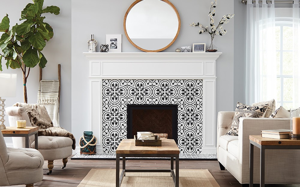A modern fireplace remodel with black and white tile lining the edges of the fireplace