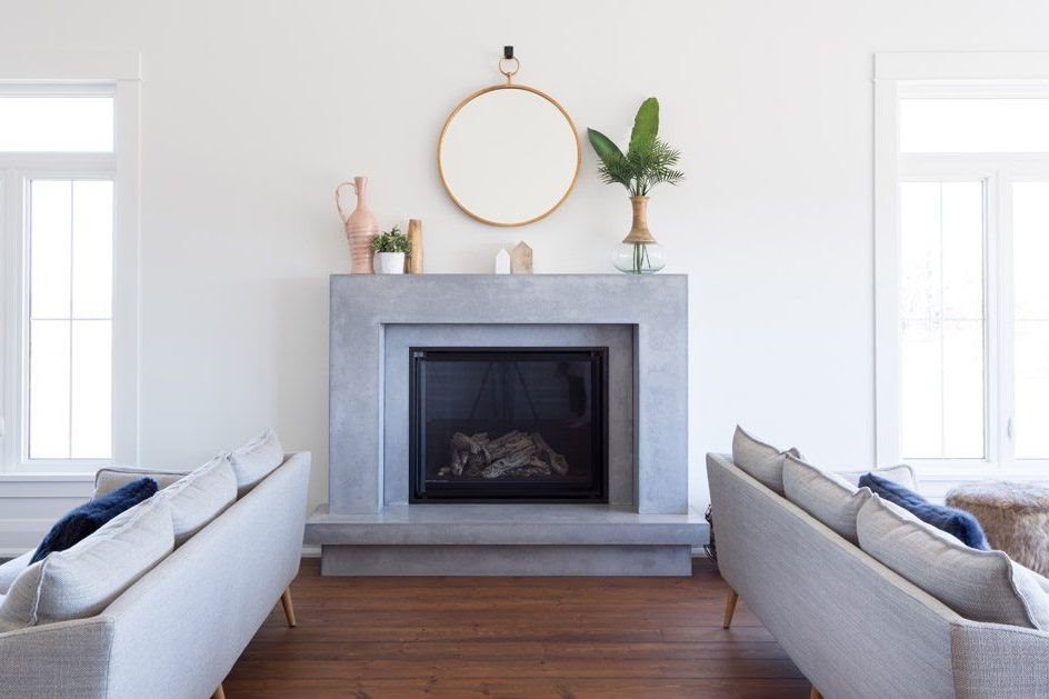 A modern fireplace remodel where the fireplace exterior is made of a smooth, grey stone