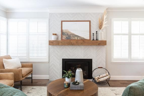 A modern fireplace remodel with a herringbone-patterned, grey and white fireplacee