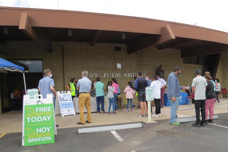 Community members stand in the parking lot in front of a church. They are standing in line and filling out forms on clipboards.