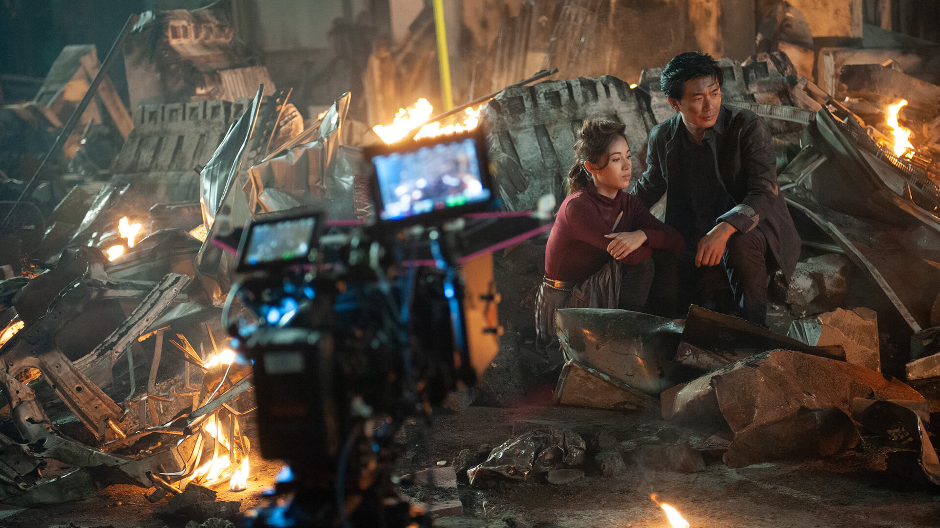 Man and woman sitting in what remains of a destroyed city, a still from the movie Ultimate Energy.