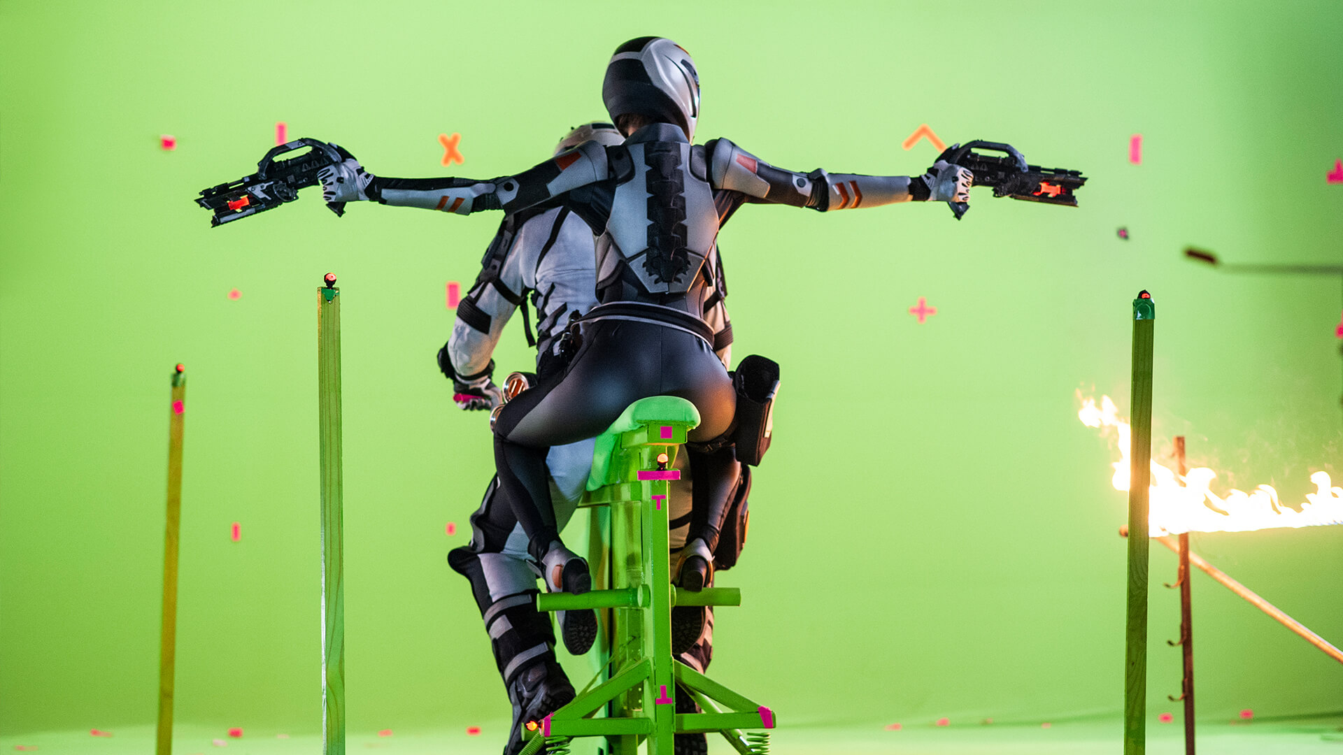 Woman holding guns on a motorcycle in front of a greenscreen, for the movie Ultimate Energy