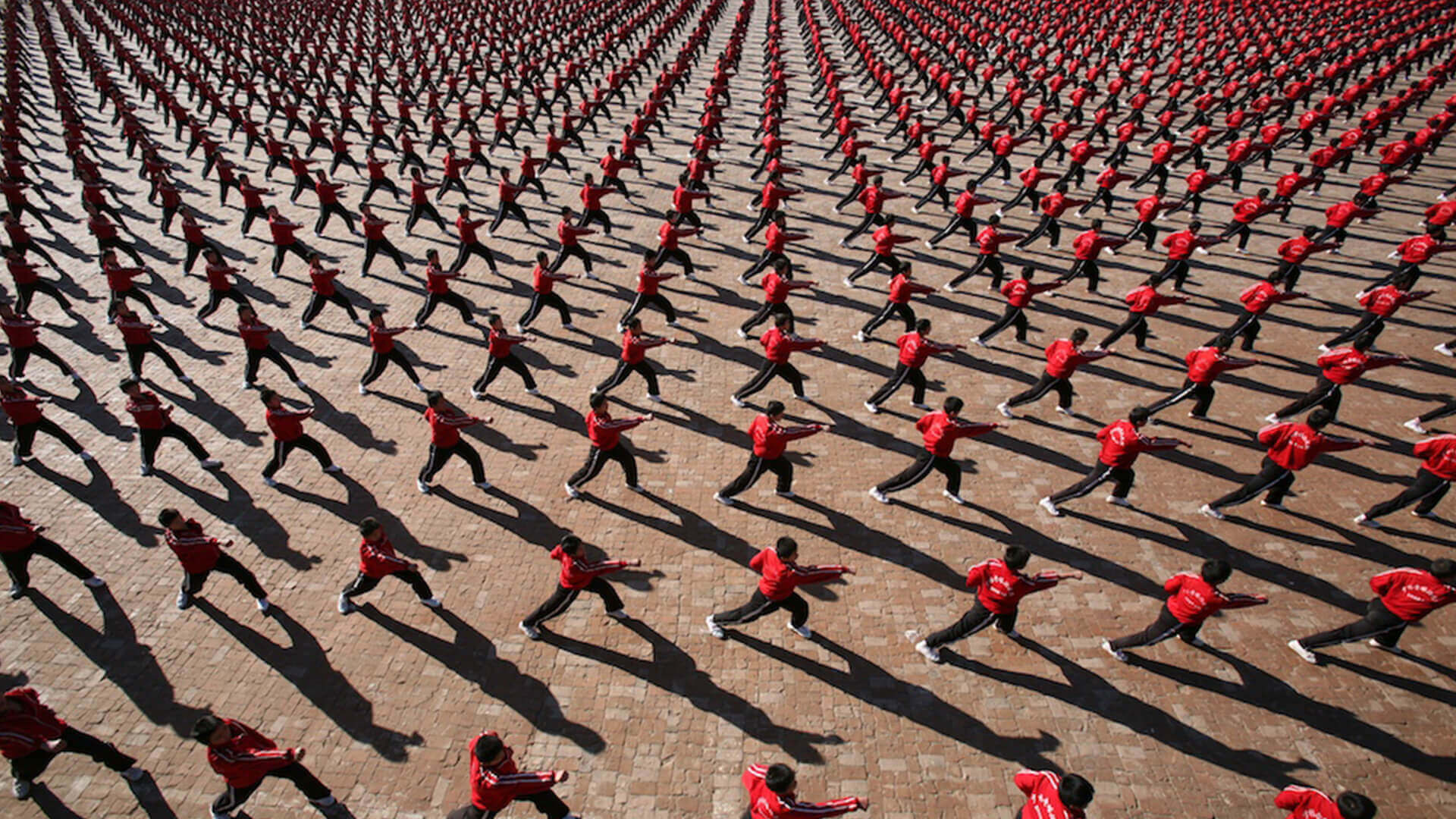 Hundreds of martial artists in red shirts, a still from the movie Samsara.