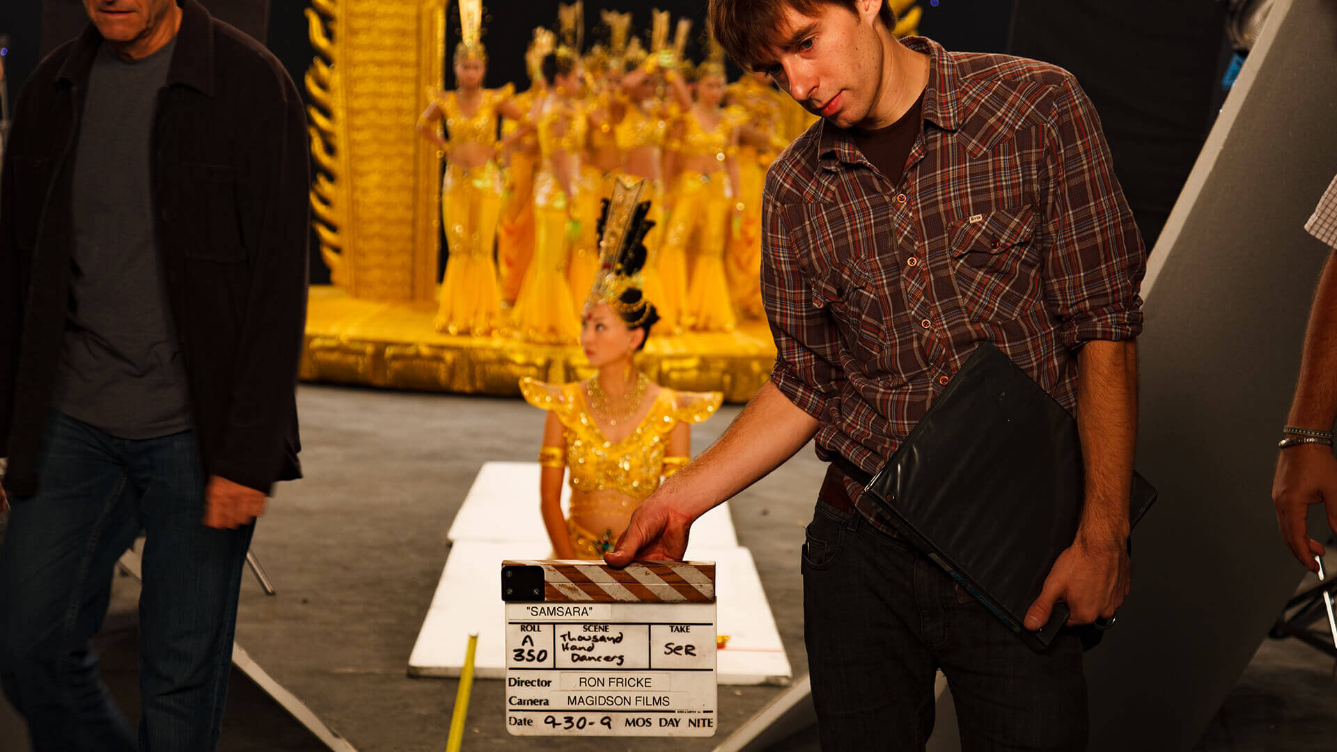 A man holding a clapper board in front of a sitting woman, a still from the movie Samsara.