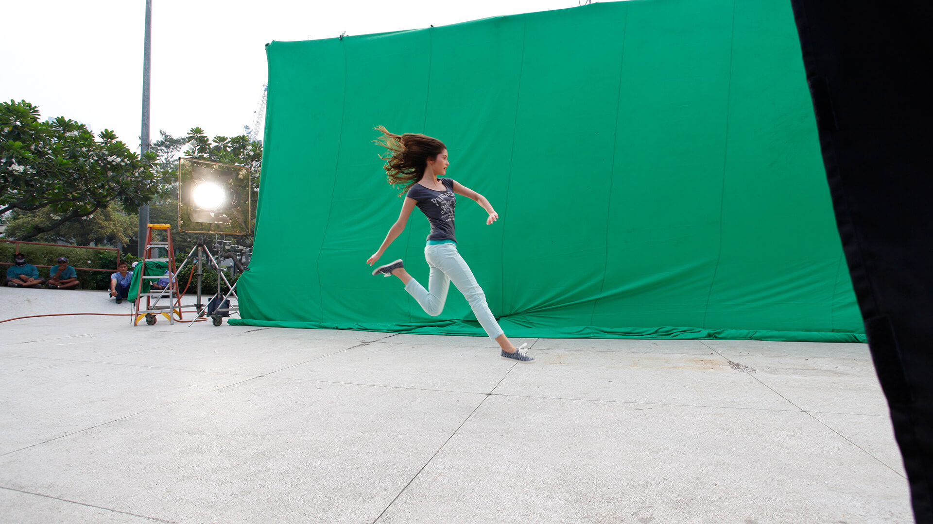 Woman jumping in front of a green screen, a still from a Sprite advertisment.