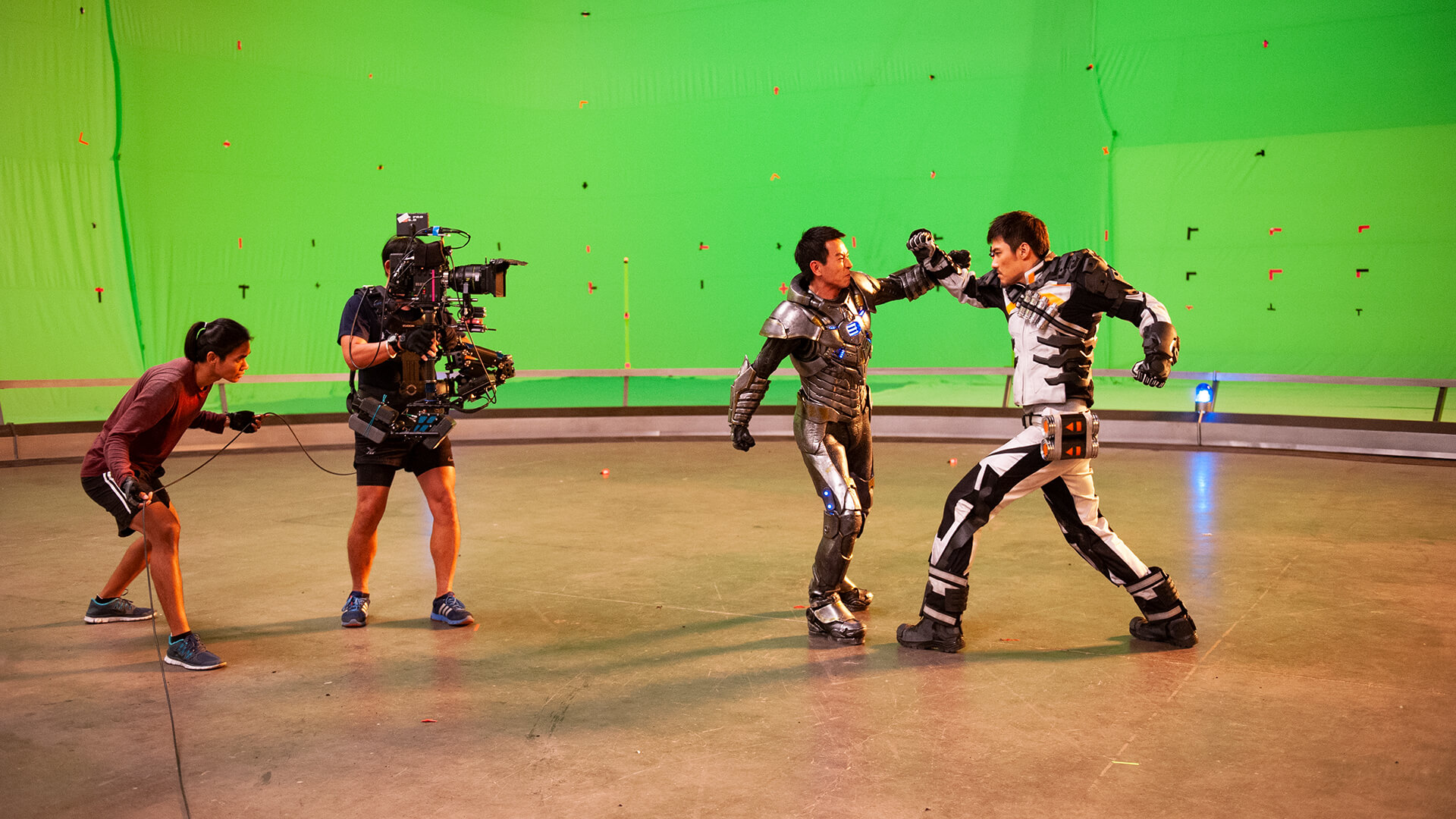 Two men fighting in power suits in front of a green screen, a still from the movie Ultimate Energy.