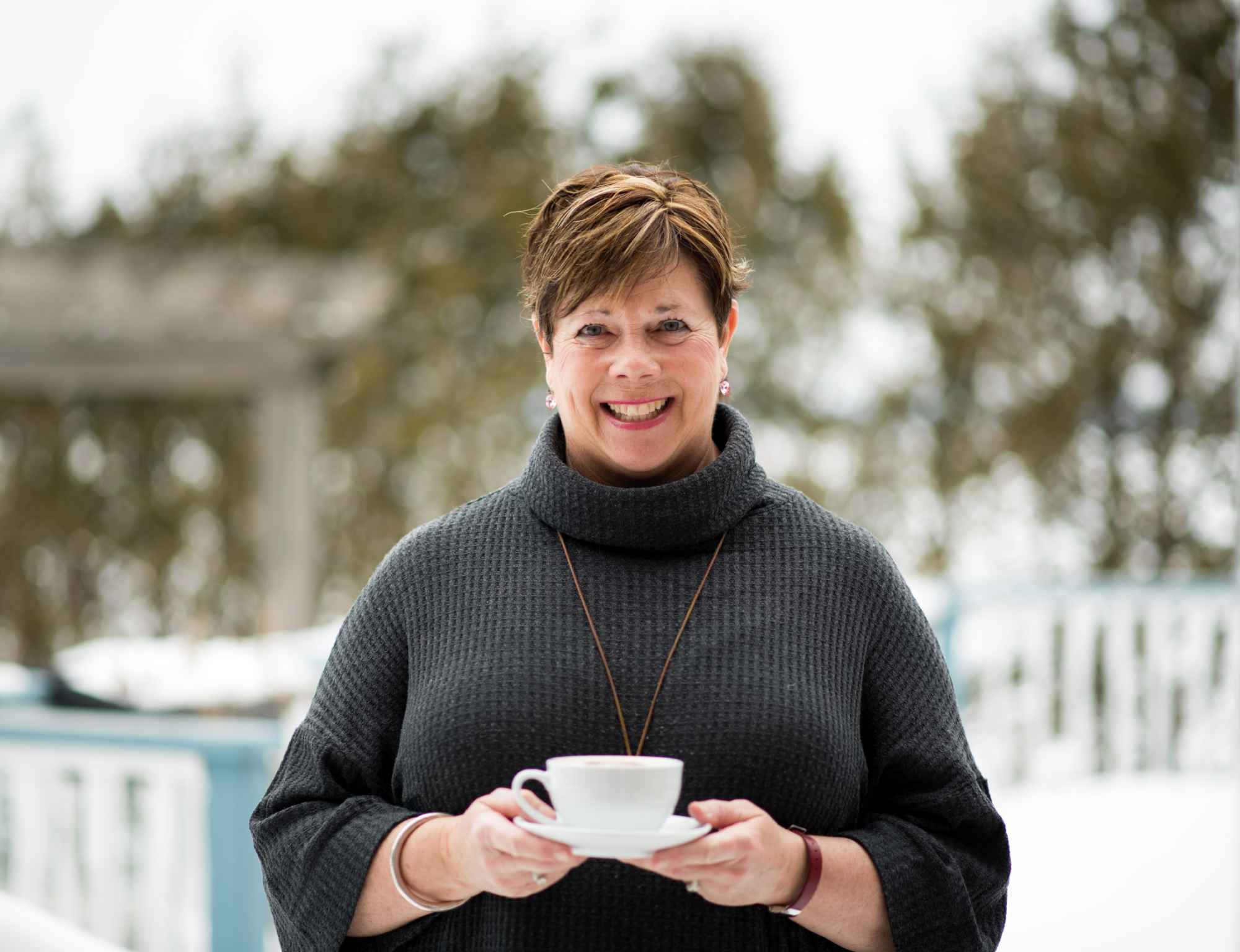 Susan, owner of The Empty Nest, holding a cup of cappuccino