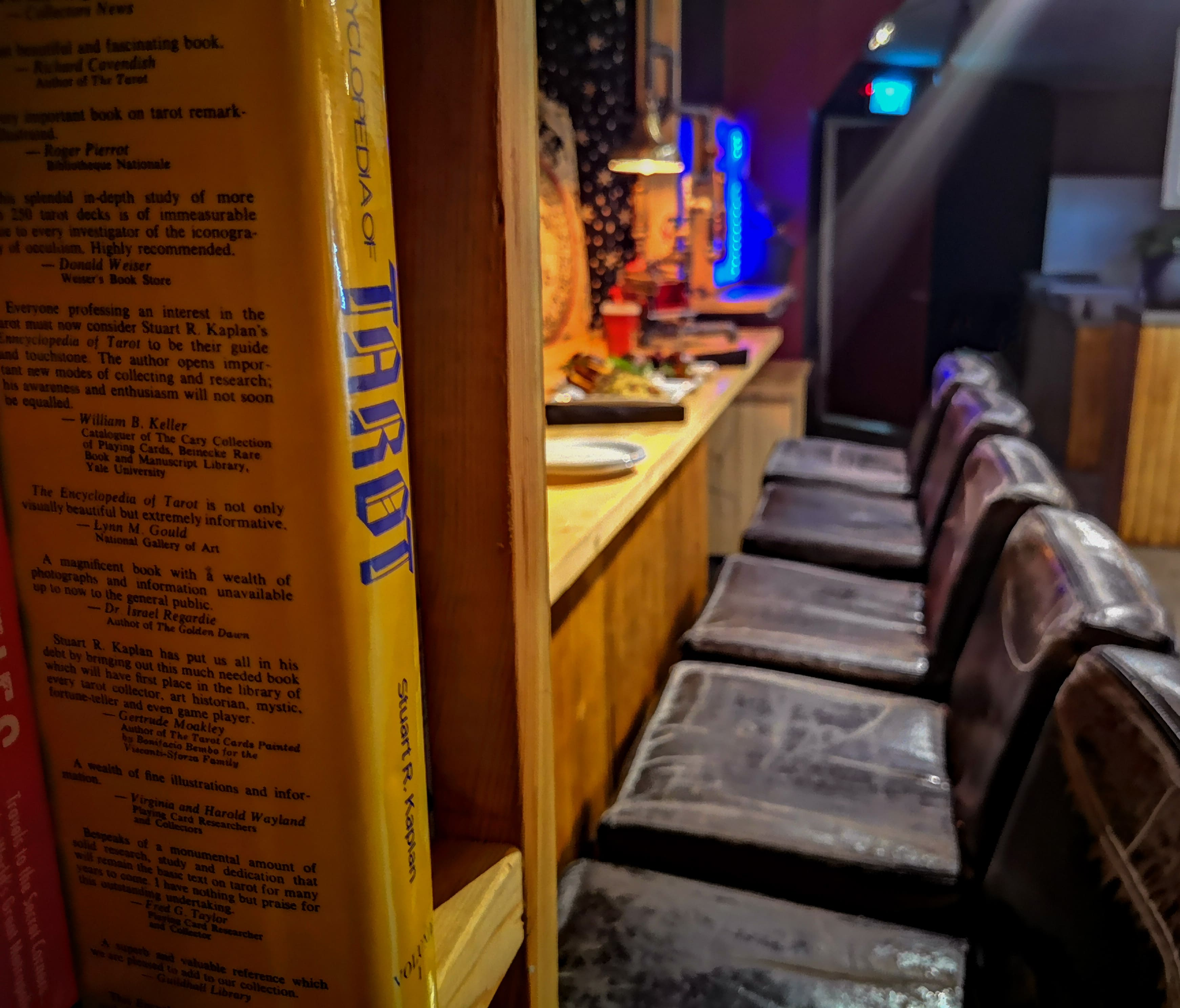 Tarot book on a bookshelf in foreground, food and drink setup on the bar in background