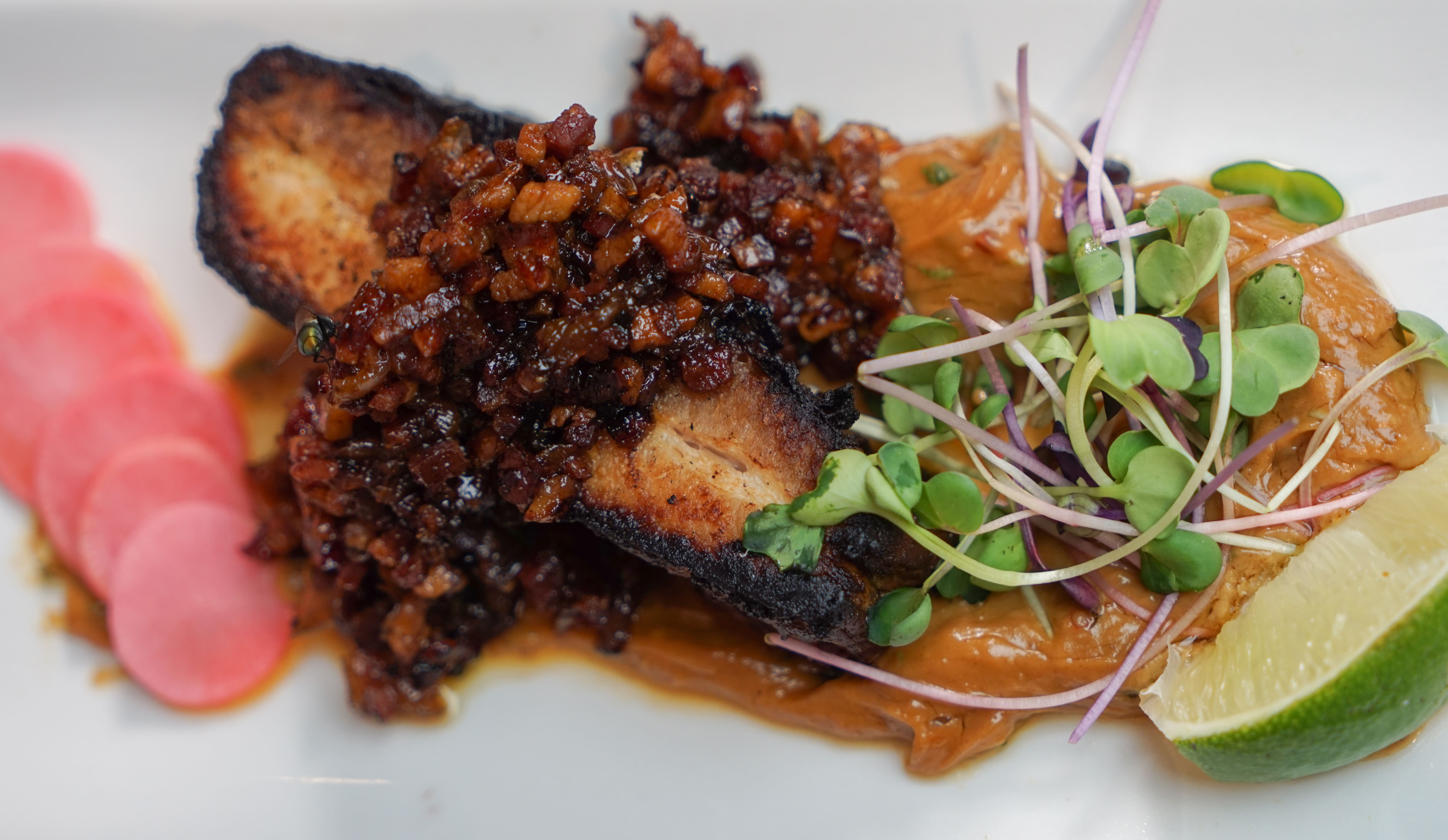 food- delicious pork belly with onion relish and fresh pea shoots