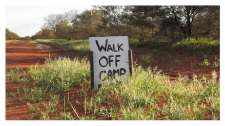 """A sign on a dirt path that reads """"Walk Off Camp"""""""