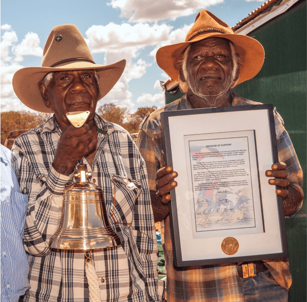 a photo of Frank Holmes holding the brass Declaration Bell and Banjo Morton holding the Declaration Bell certificate