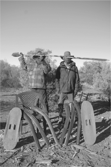A black and white photo of two Alyawarran men standing holding a piece of equipment