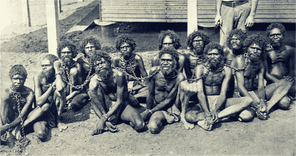 A black and white image of a group of Aboriginal people sitting with chains around their necks