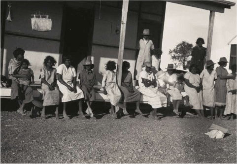 A black and white photo of Aboriginal women and children sitting on a verandah at Brunette Downs Station, Northern Territory, 1930