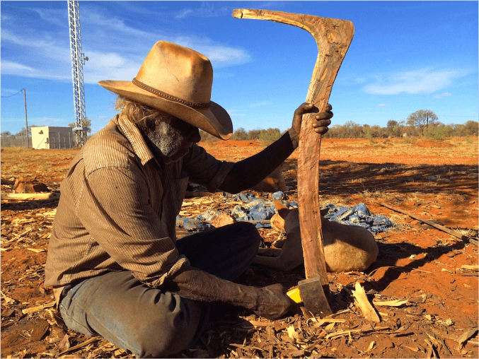 A photo of Frank Holmes carving a number 7 boomerang.