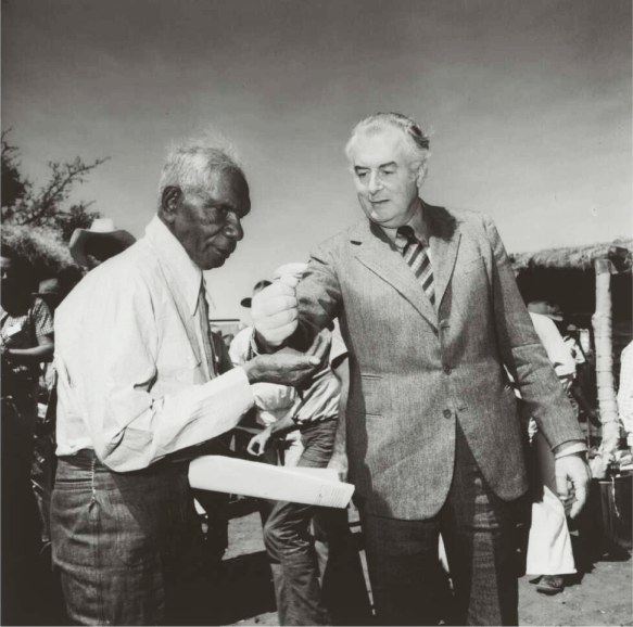 A black and white photo of Prime minister Gough Whitlam pours soil into the hand of Gurindji Traditional Land Owner Vincent Lingiari at Wattie Creek, Northern Territory, 16 August 1975. Source: National Library of Australia