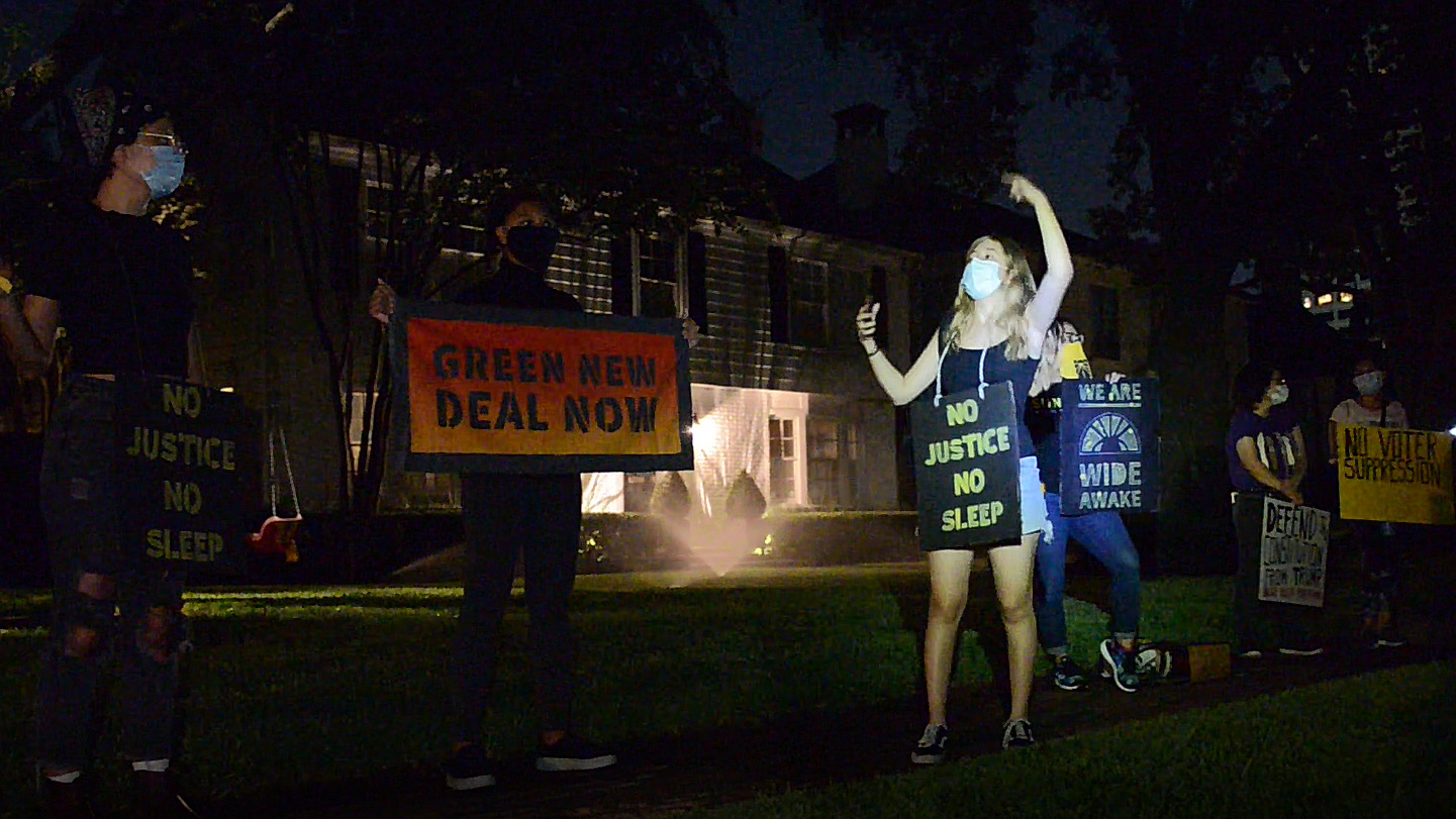 """Young people protesting in night with signs saying """"No justice, no sleep"""" and """"Green New Deal Now"""""""