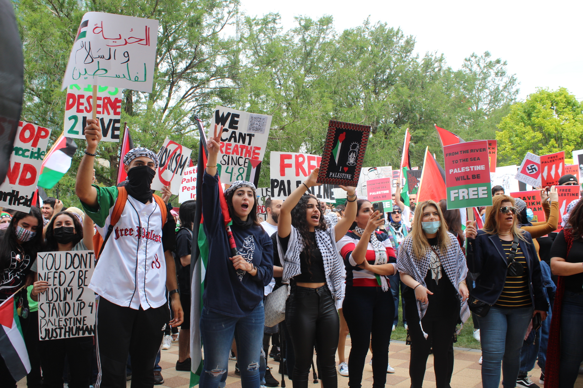 Youth and adults holding signs in support of Palestine