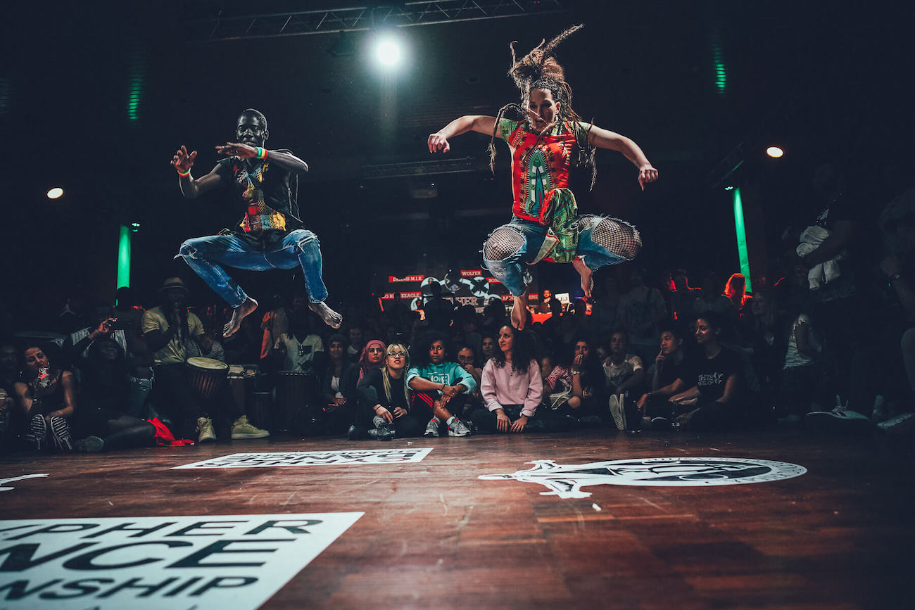 Two street dancers jumping in a dance battle surrounded by a crowd.