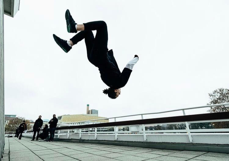 An urban dancer doing a parkour jump.