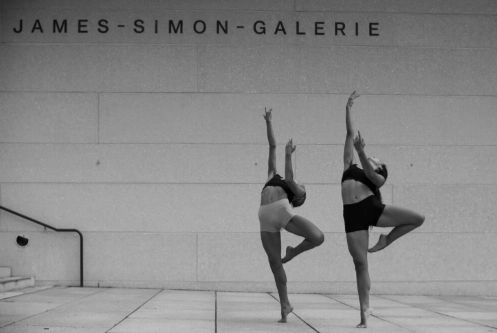 In black and white, two girls in a ballet pose in front of the James-Simon-Galerie in Berlin.