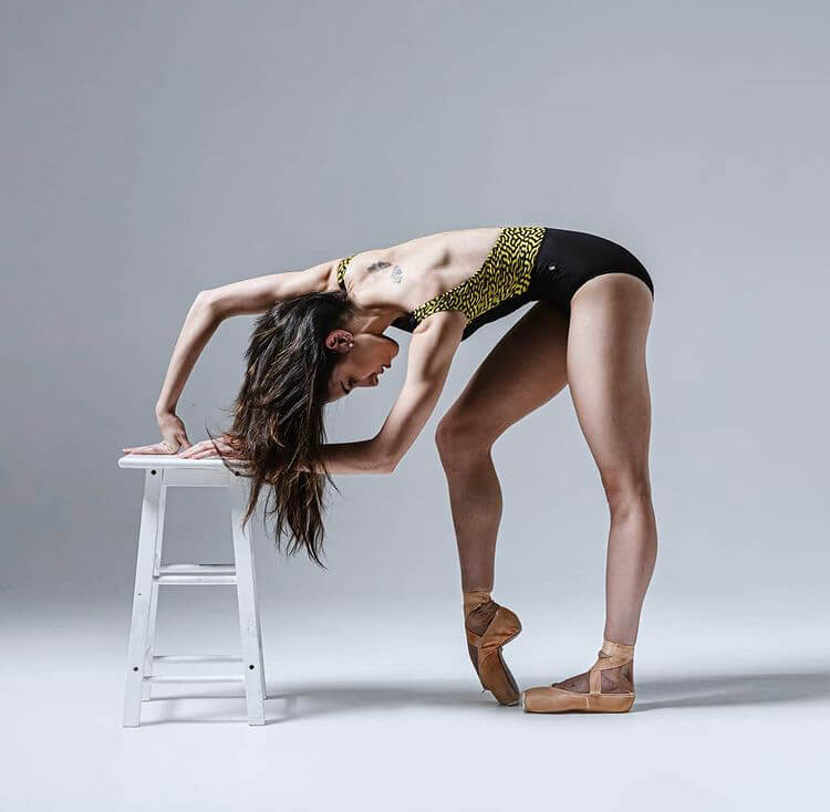 Ballet dancer posing in a black and yellow ballet bodysuit.