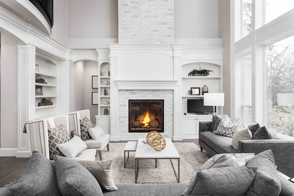 Beautiful, modern living room which features a large fireplace and windows.