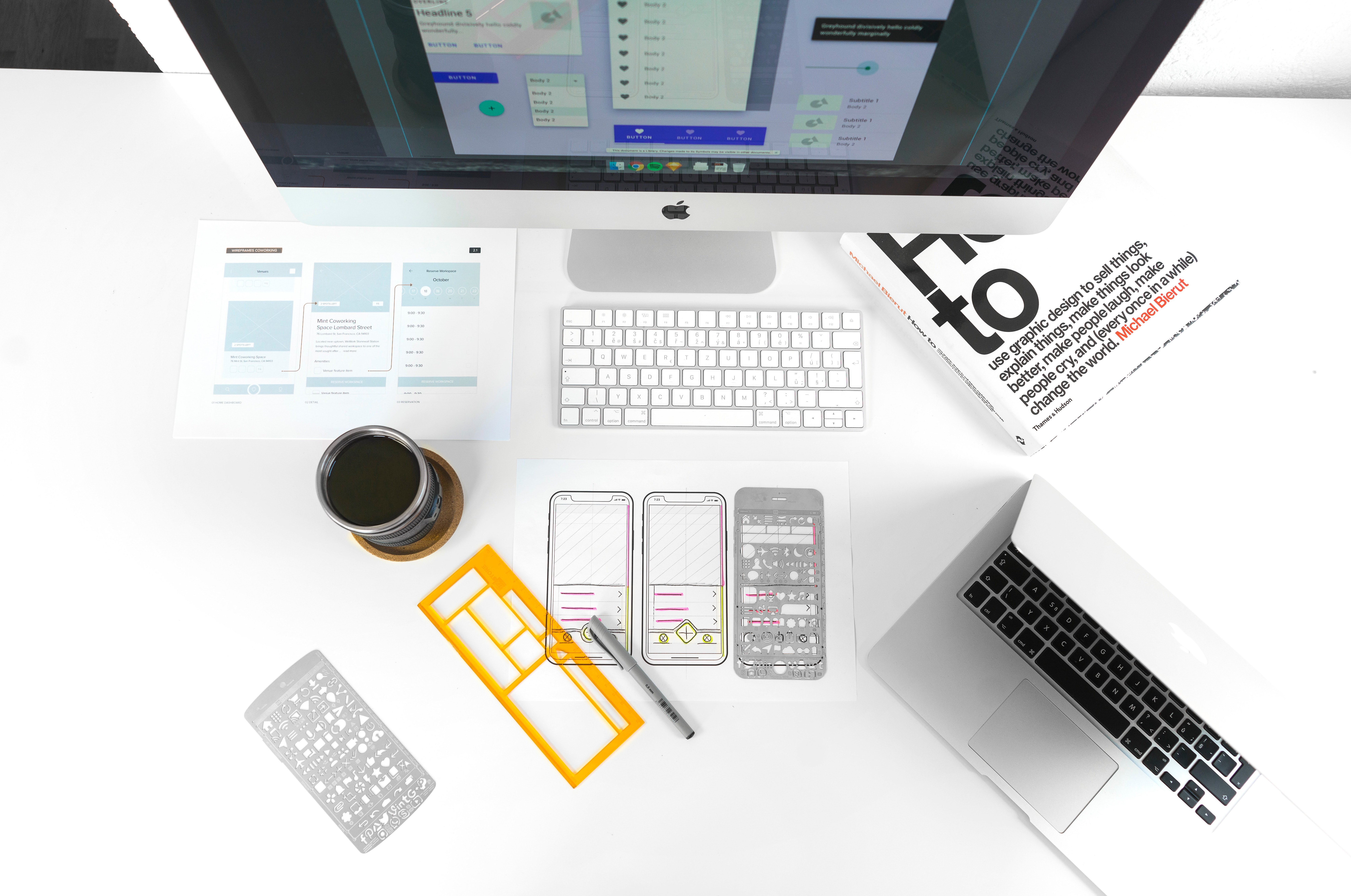 Aerial view of a desktop with a keyboard, coffee, laptop, graphic design book, and prototyping drawing templates for mobile phone