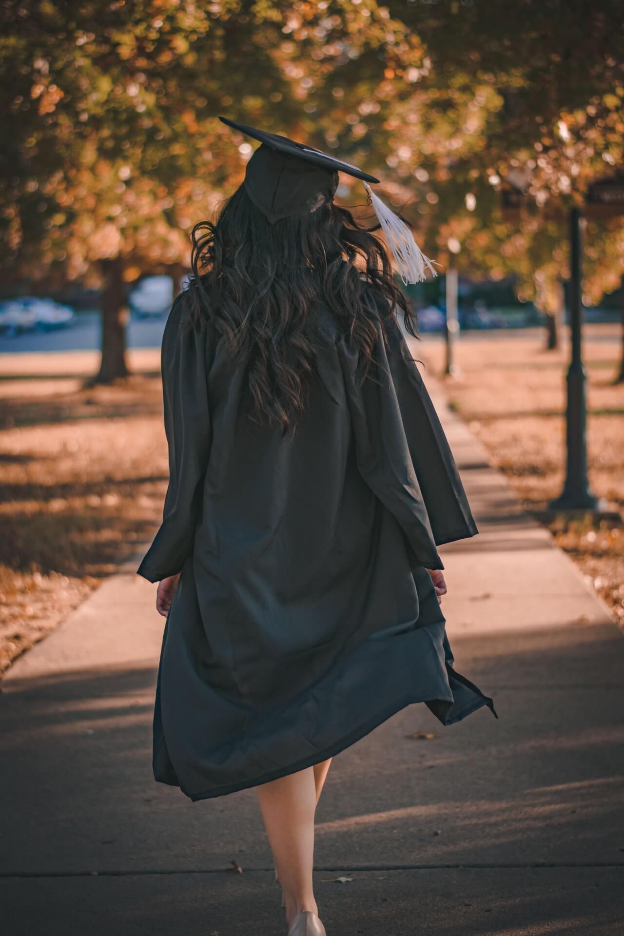 girl walking with graduation cap