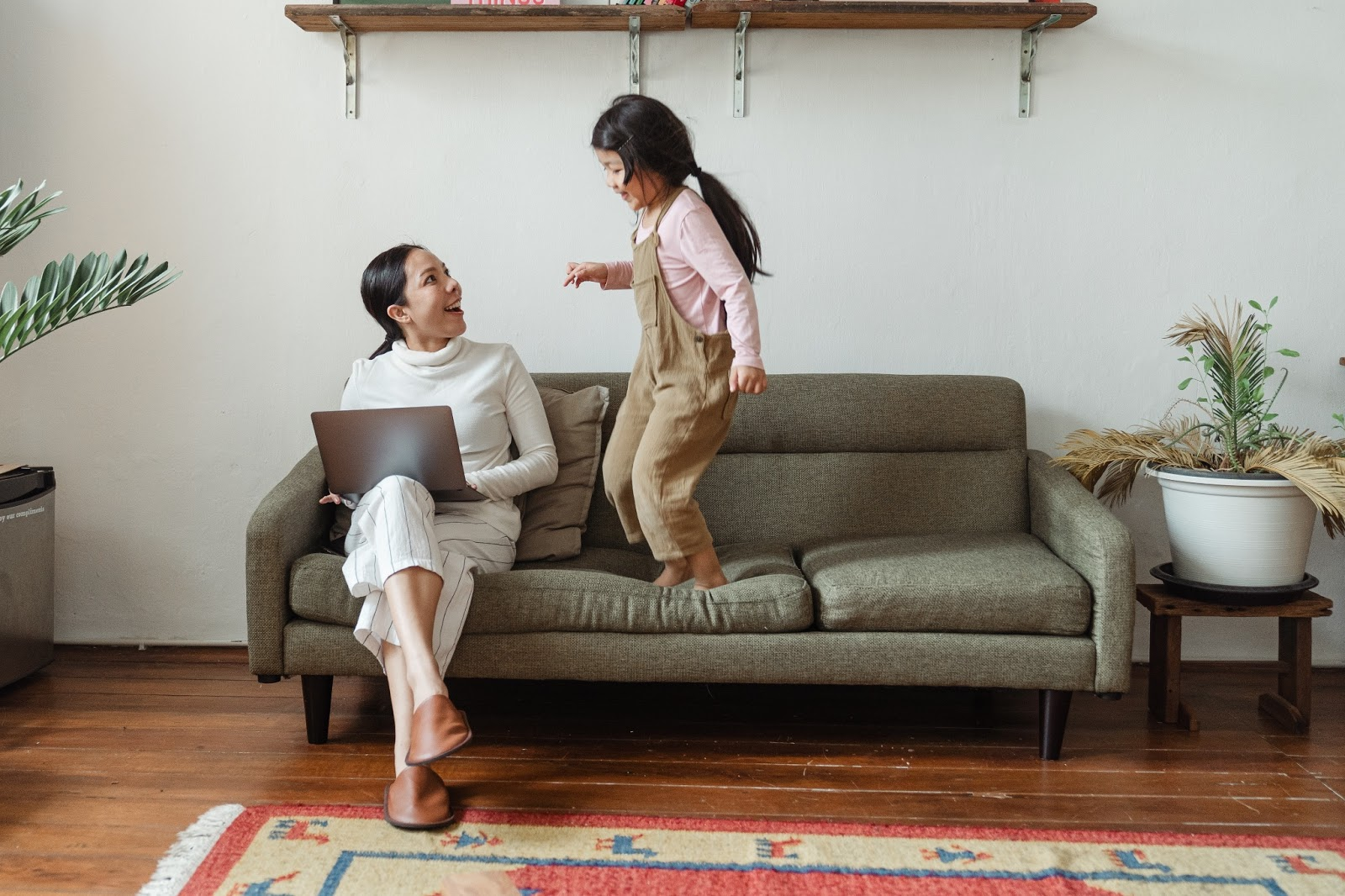 Mom working on computer with daughter jumping on couch next to her