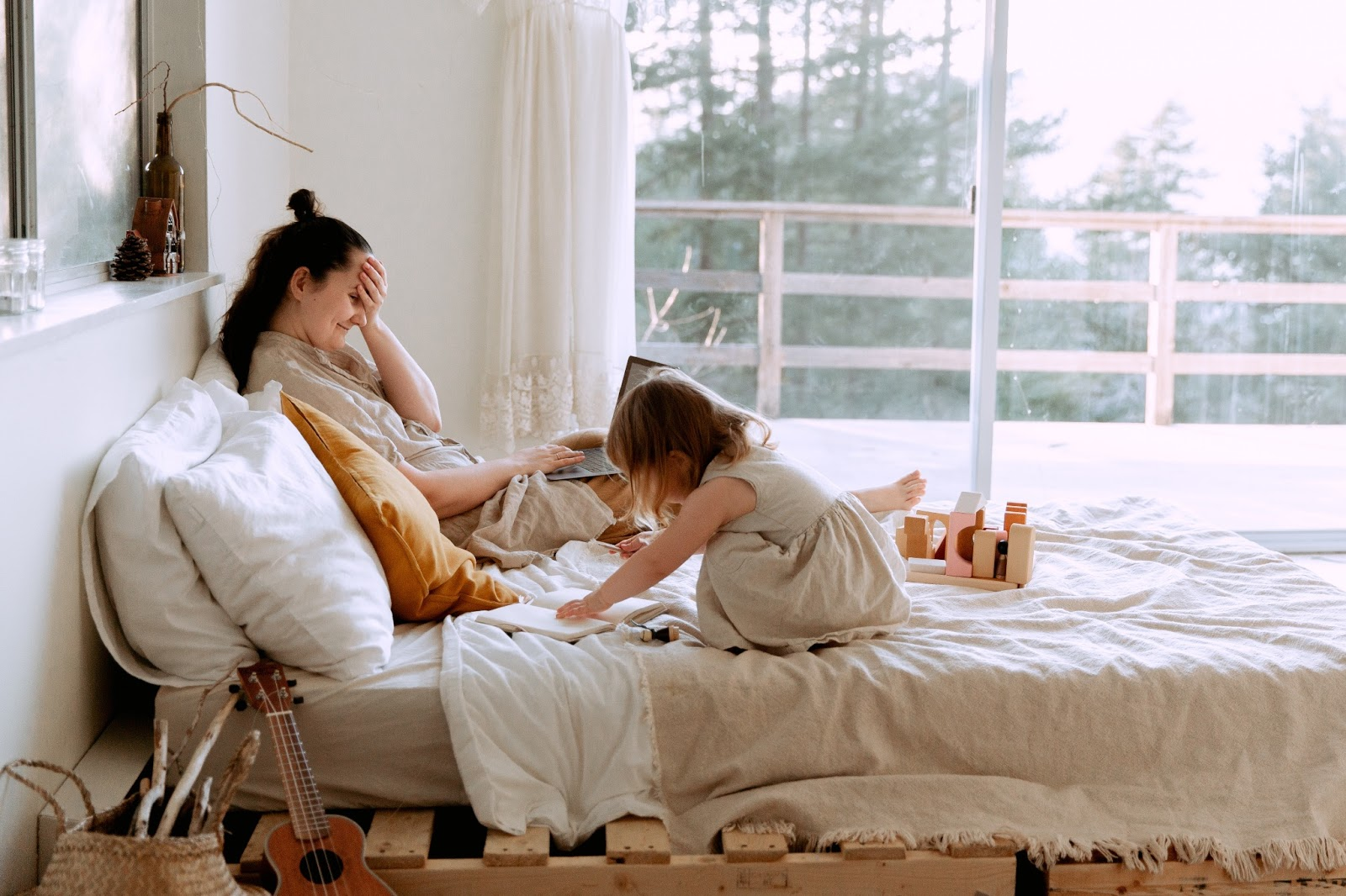 Mother and child relaxing on bed together
