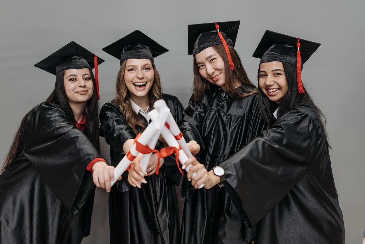 Four graduates holding their diplomas