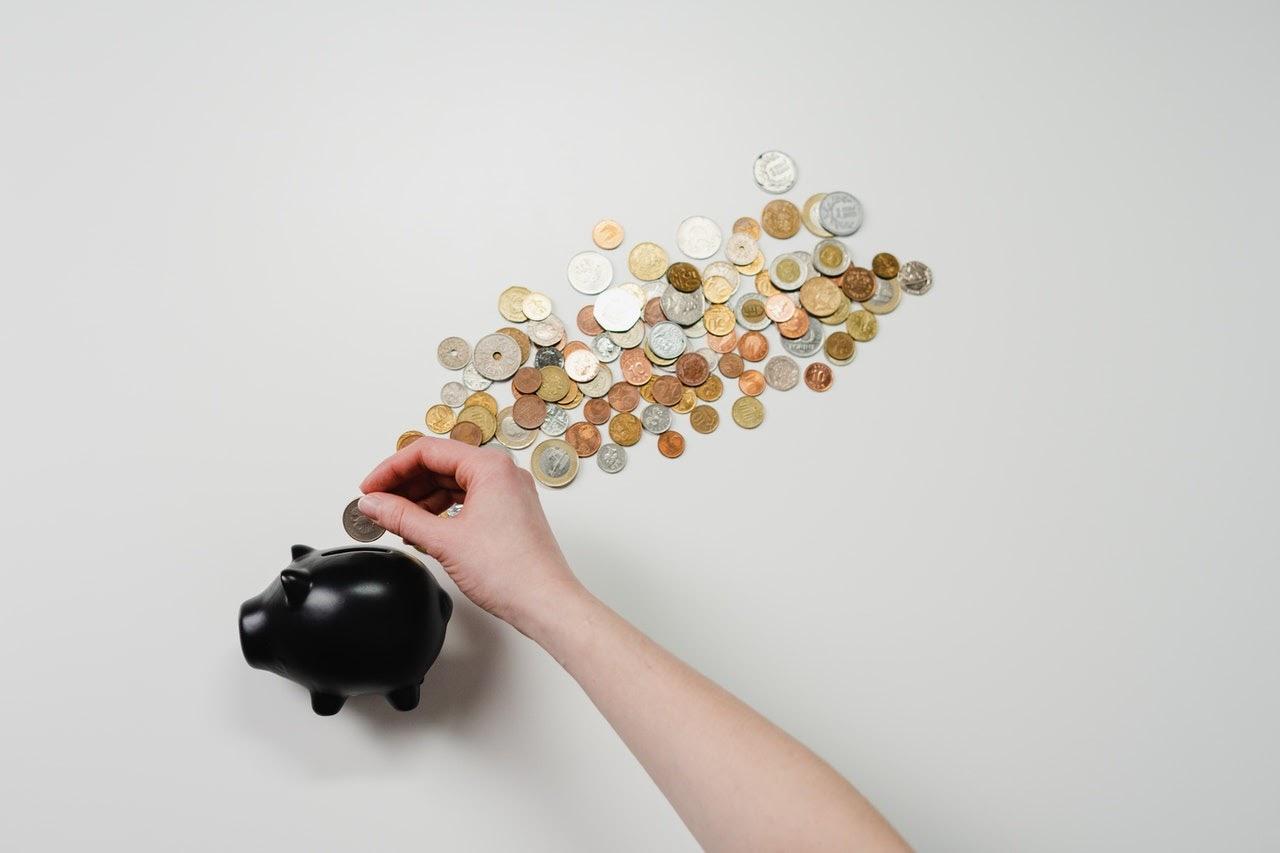 Hand placing coin into piggy bank