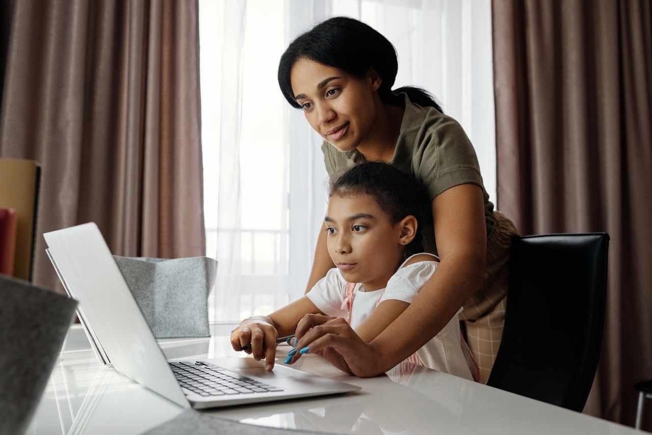 Mother helping child on comput