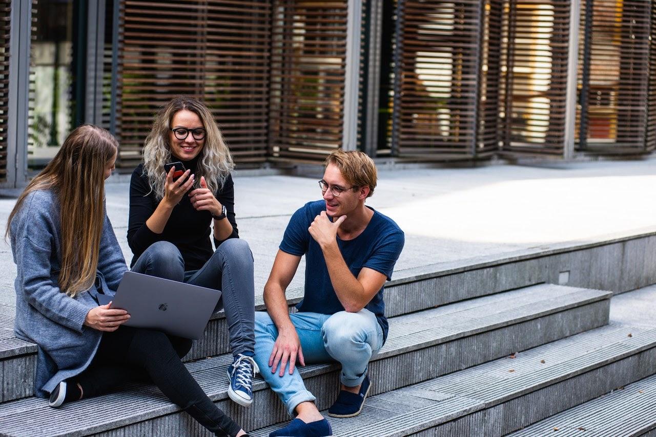 Three students sitting on steps