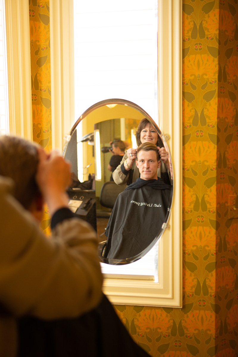 Young man viewing hair cut in mirror