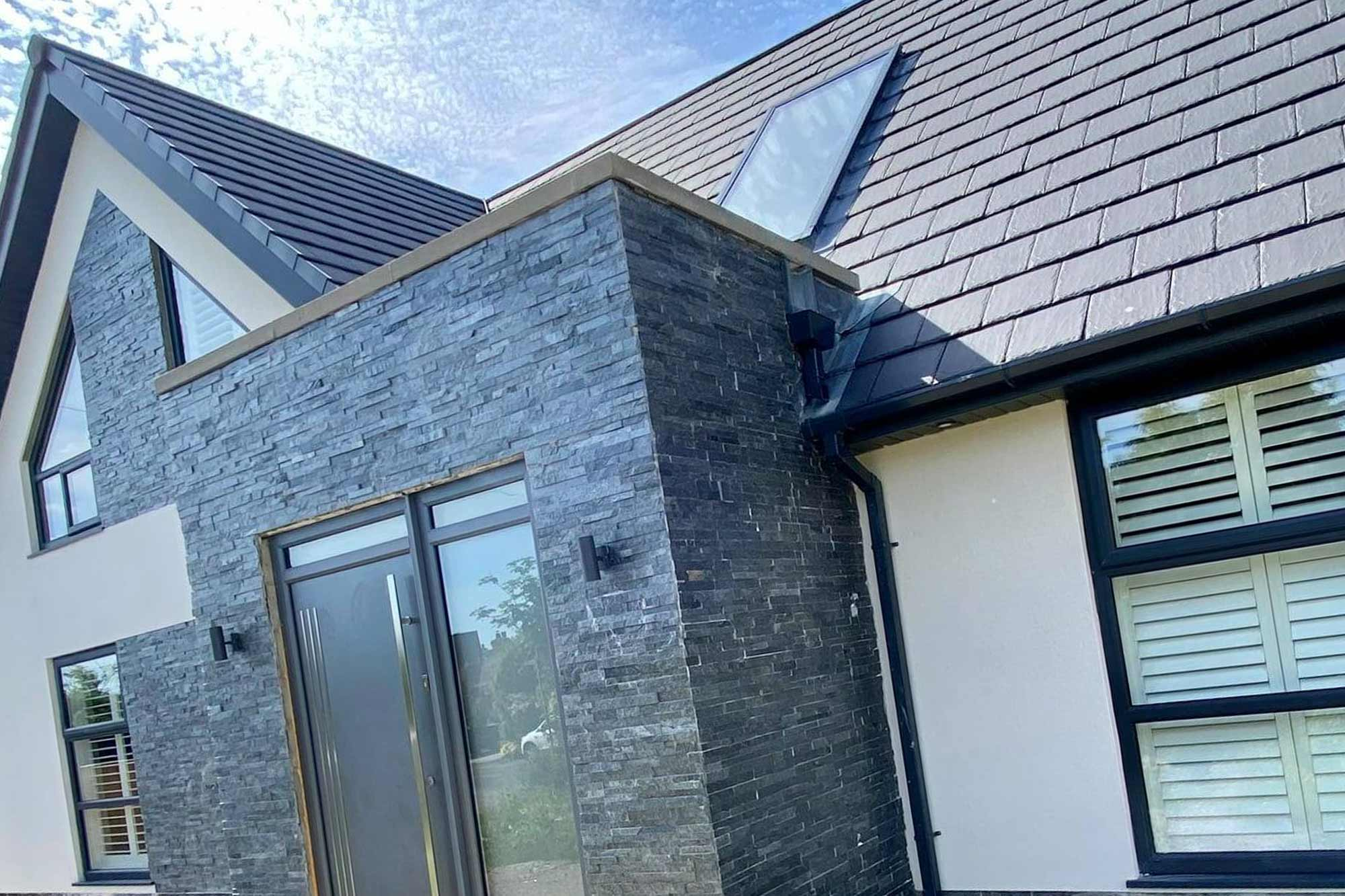 Modern extended bungalow front elevation with slate cladding porch