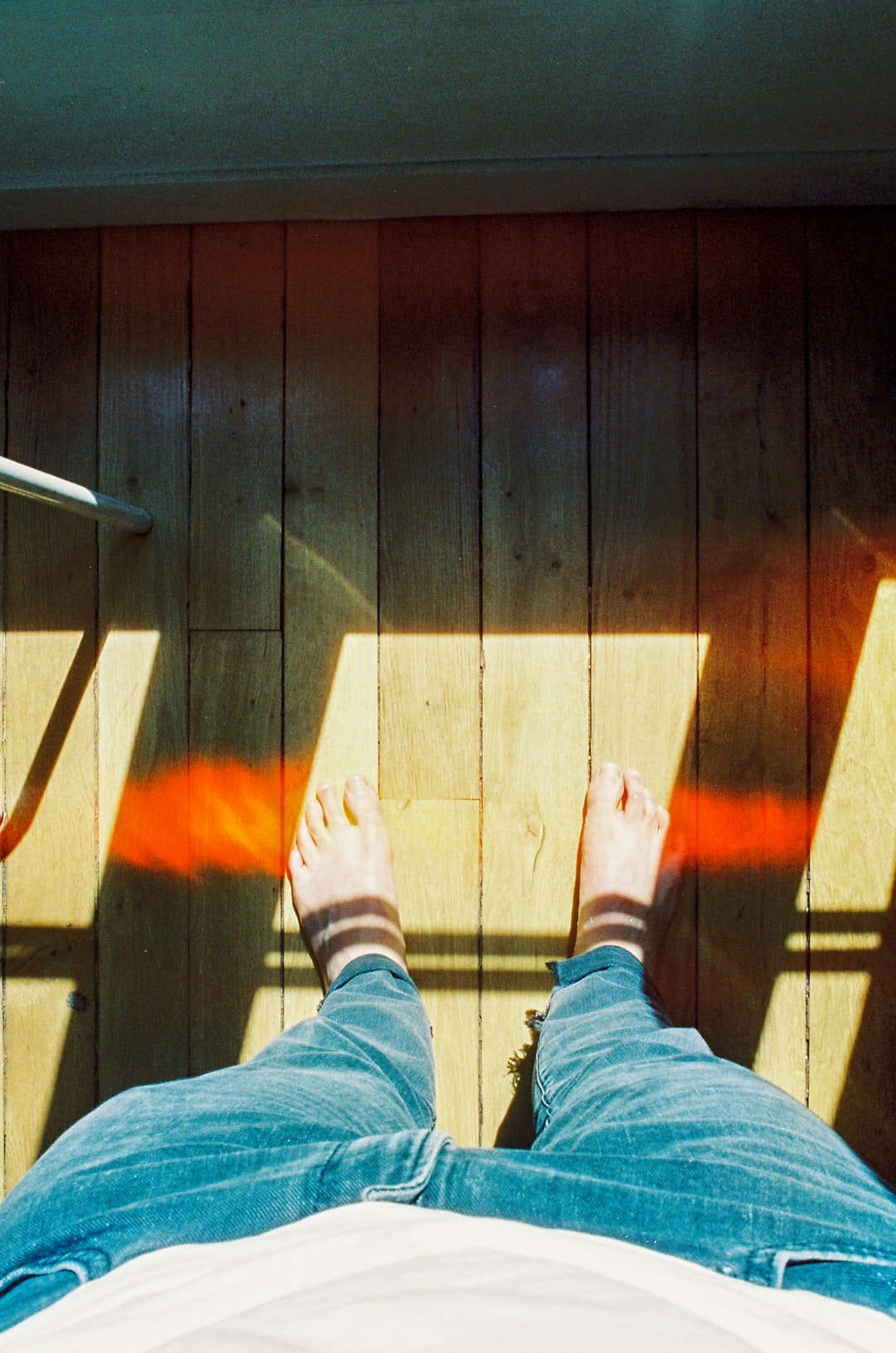 person in blue denim jeans standing on brown wooden floor