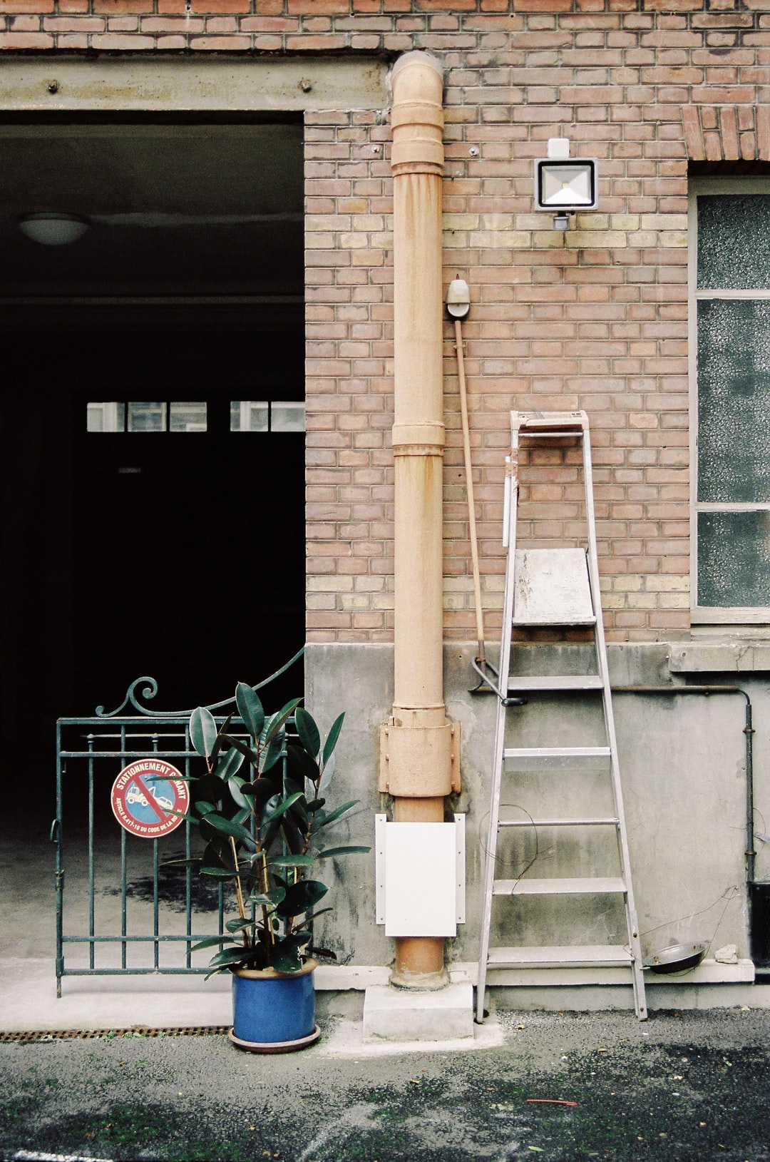 white ladder leaning on brown brick wall