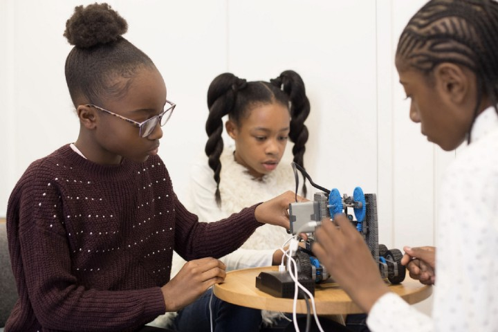 A group of young black girls creating with robotics