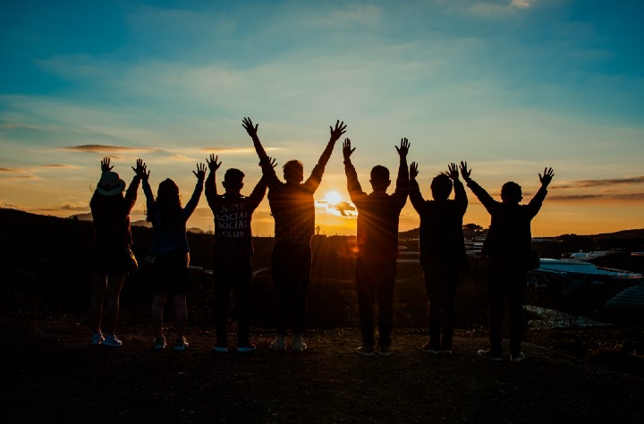 A group of people with their hands up towards the sunset