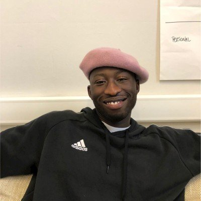 A picture of Richard Fagbolagun wearing a pink beret