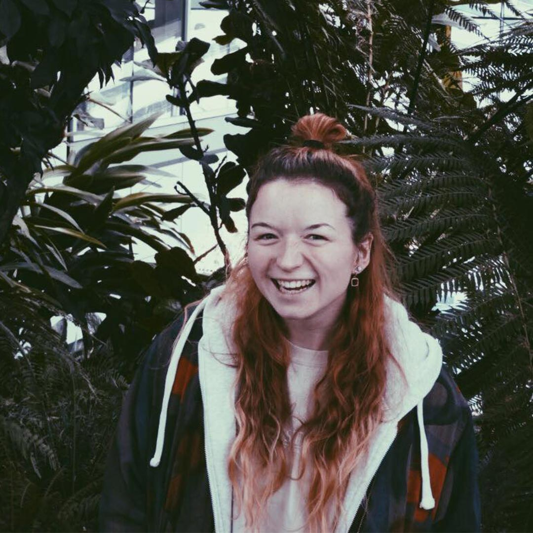 Woman smiling with a backdrop of foliage.