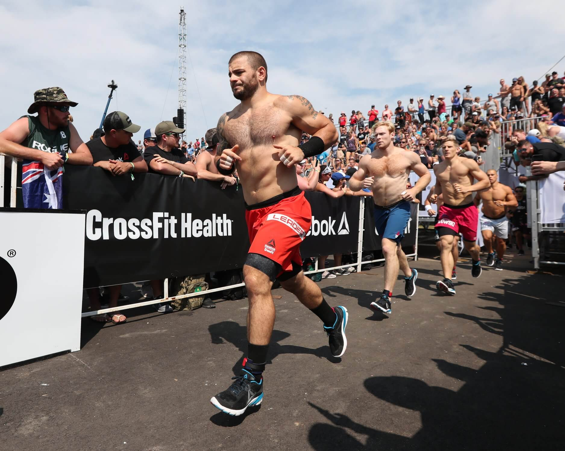 mens running through a crowd during the CrossFit Games