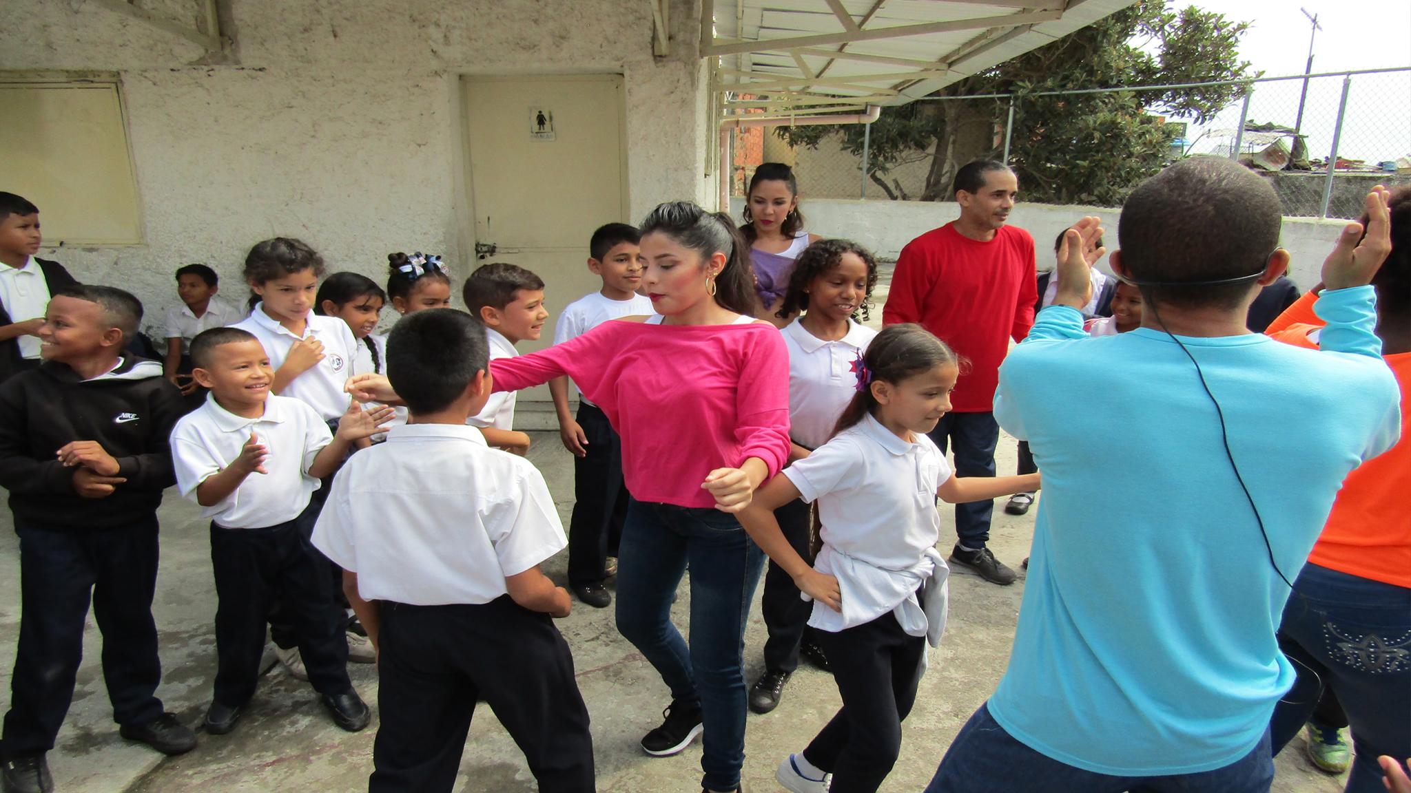 Niños bailando en el patio del colegio durante el taller