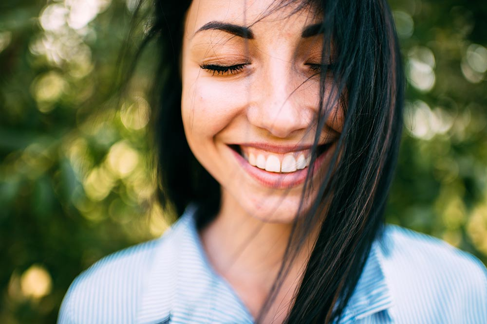 Woman with dark hair smiling with her eyes closed