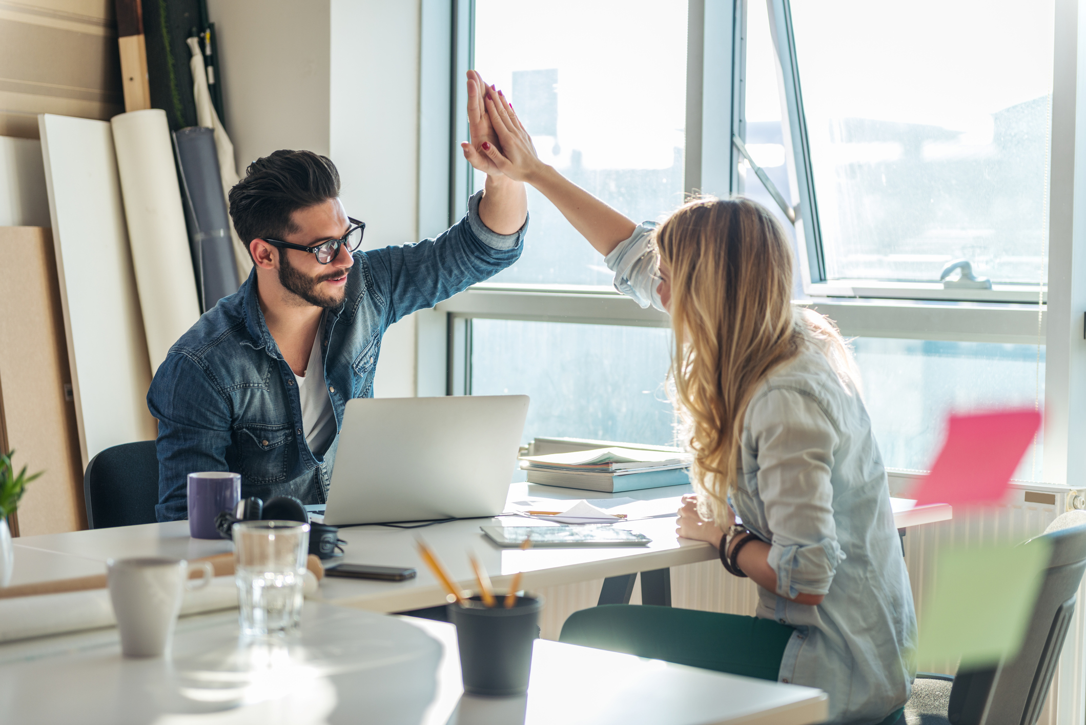 Happy co-workers high-fiving celebrating a successful marketing campaign