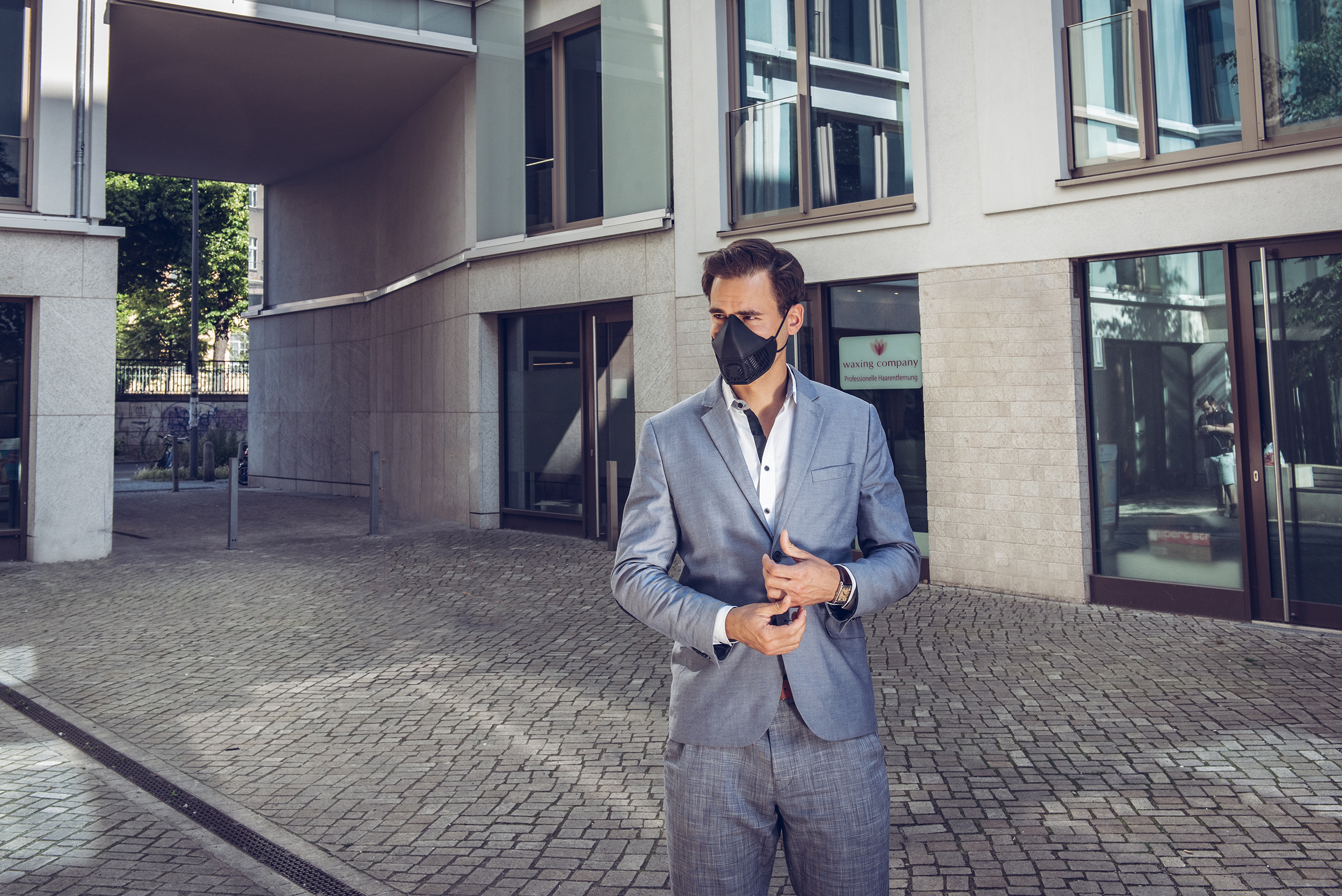 Man wearing black silicone facemask in a suit.