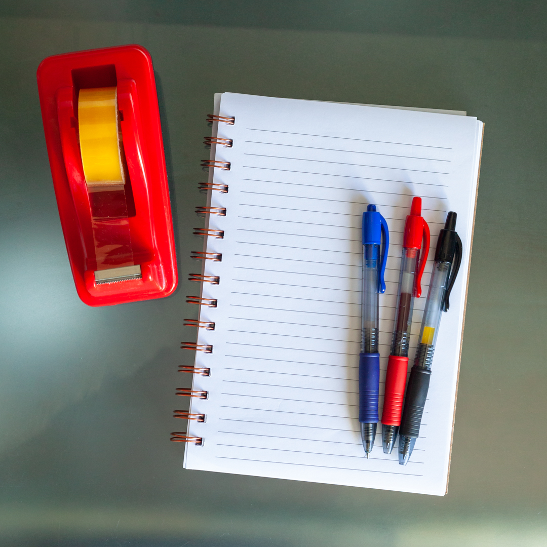 A reel of sticky tape and a notepad and pens used for creating thinking.